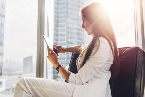 Erfolgreiche Frau Anzug sitzt auf Sessel mit Tablet-PC auf ihre Loft-Wohnung im Stadtzentrum – Foto