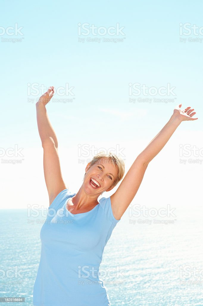 Successful  woman with hands raised by the sea stock photo