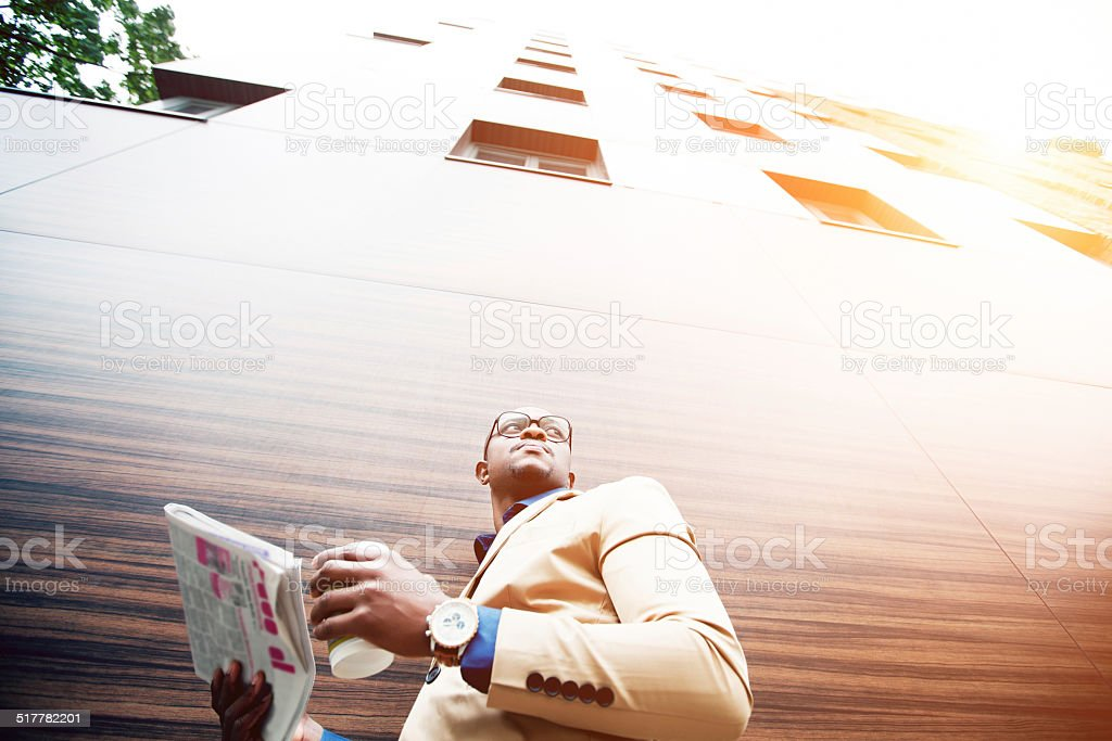 Successful young african man reading a newspaper while drinking coffee stock photo