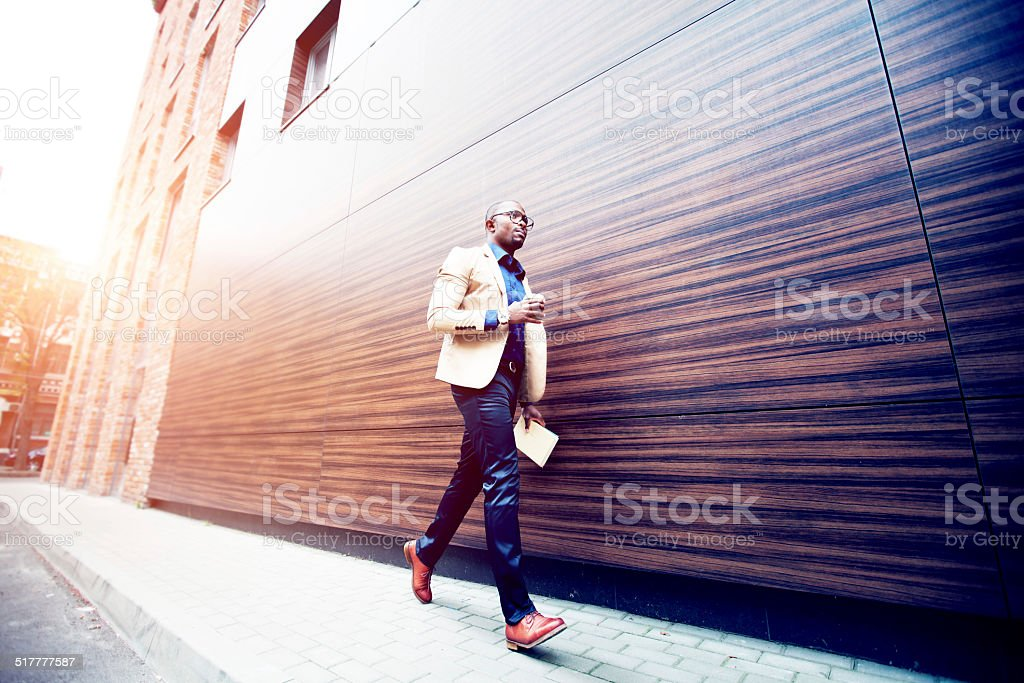 Successful young african man with book and coffee stock photo