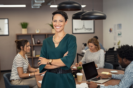 Portrait of successful business woman standing with her colleagues working in background at office. Portrait of cheerful fashion girl in green dress standing with folded arms and looking at camera. Beautiful businesswoman feeling proud and smiling.