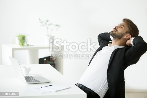 istock Successful young businessman in suit relaxing at workplace breathing air 918364572
