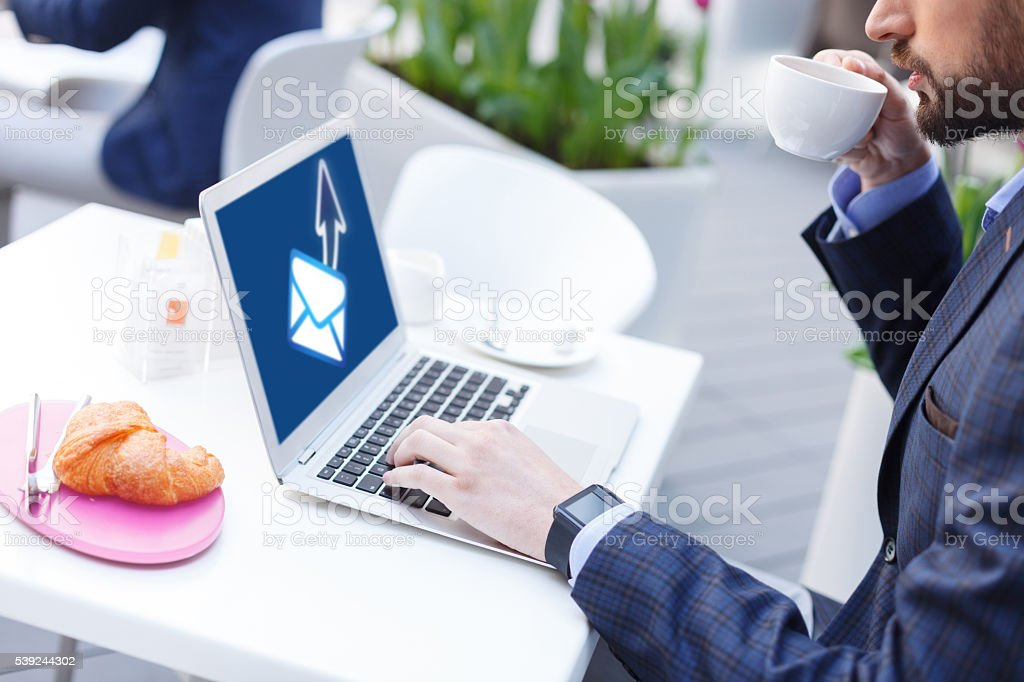 Successful young businessman using laptop in cafe royalty-free stock photo