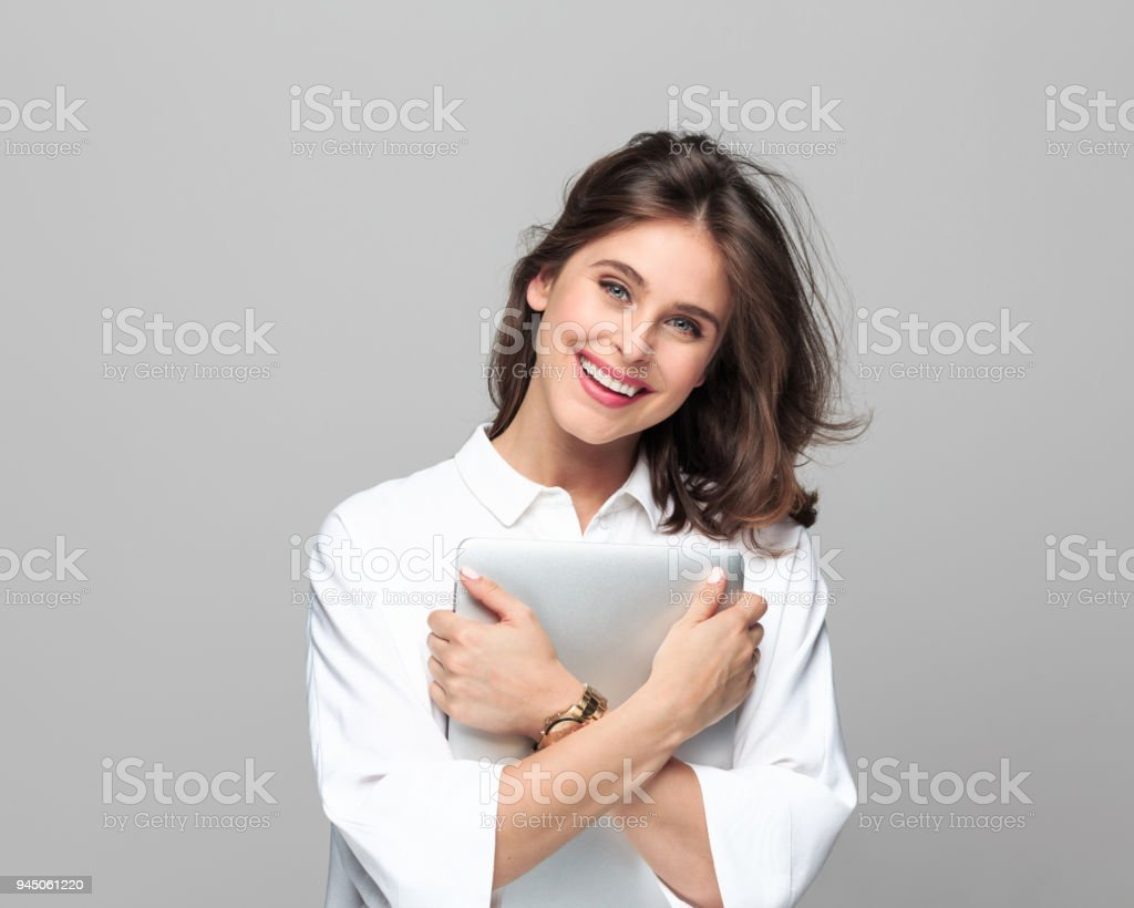 Successful young businesswoman holding laptop Happy young businesswoman holding a laptop, standing against grey background. 25-29 Years Stock Photo