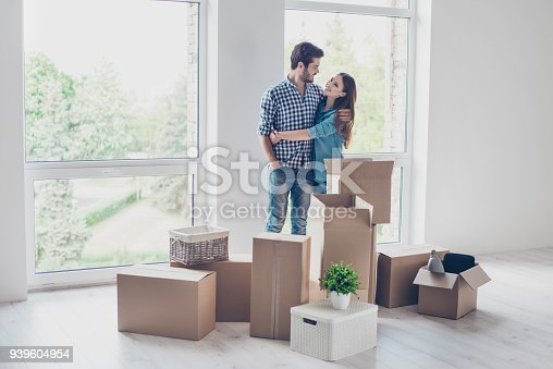 istock Successful young couple is moving to new nice place and embracing, around are carton boxes with their belongings. The room is very light and bright, they are wearing casual outfit 939604954
