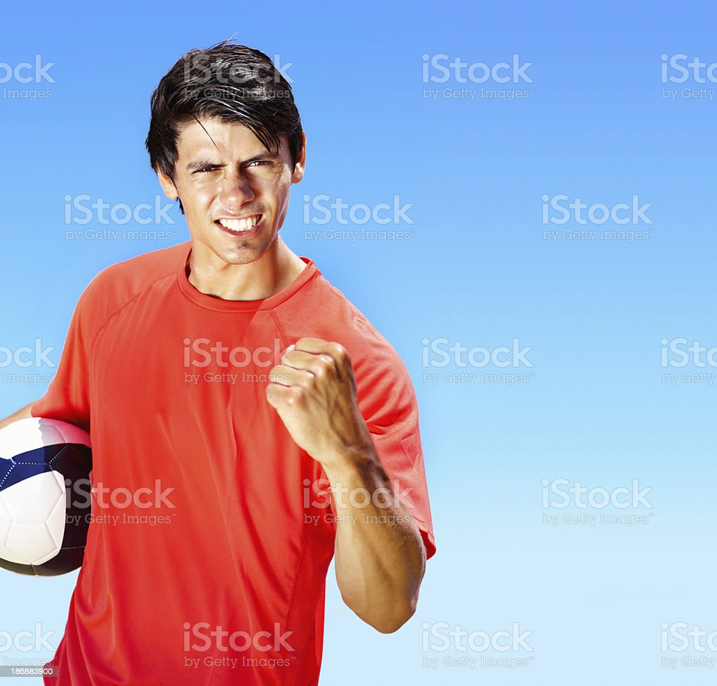 Successful young footballer with football against blue sky royalty-free stock photo