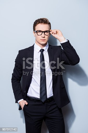 973213156 istock photo Successful young handsome businessman banker in a suit is fixing his glasses, he stands on pure light background. So mature and virile, hot and confident 937312142