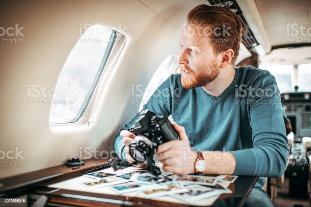 Rich young redheaded man sitting inside a private jet and looking at...