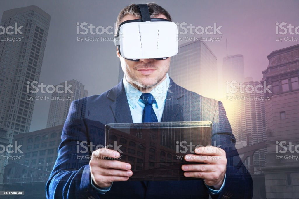 Successful young man working with VR headset and tablet computer stock photo
