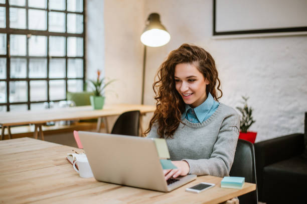 Successful young woman in modern office working on laptop. stock photo