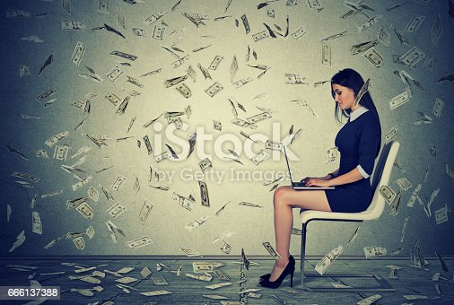 istock Successful young woman using a laptop sitting on a chair 666137388