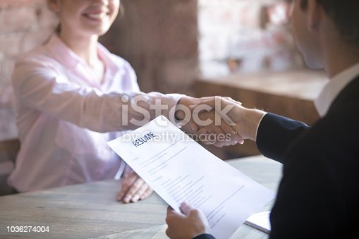 Smiling young woman and man handshake. Businesspeople shaking hands. Human resources, successfully passing the interview, hr concept. Close up resume paper