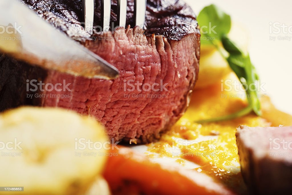 Succulent rare grilled fillet steak being sliced royalty-free stock photo