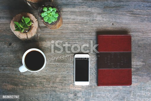istock Succulents in Wood Pots, Coffee Cup, Leather Notebook and Phone Border Over Rustic Background, Horizontal 853652792
