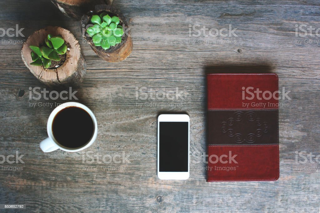 Succulents in Wood Pots, Coffee Cup, Leather Notebook and Phone Border Over Rustic Background, Horizontal stock photo