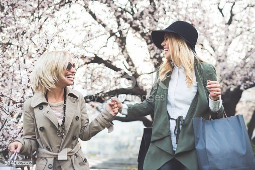 Two attractive ladies feeling happy after shopping.