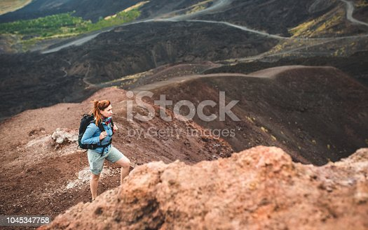 Young woman hiking alone on Etna volcano