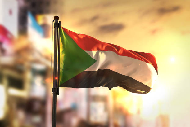 sudan flag against city blurred background at sunrise backlight - sudan stock photos and pictures