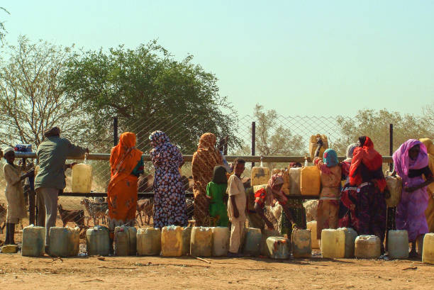 Sudanese women waiting in line to fetch water in Al Fashir, capital of North Darfur, Sudan. Al Fashir, Sudan - 22 Dec 2009: Sudanese women waiting in line to fetch water in Al Fashir, capital of North Darfur, Sudan. omdurman stock pictures, royalty-free photos & images