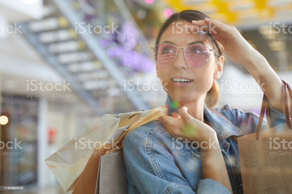 Young attractive girl in pink sunglasses going shopping while...