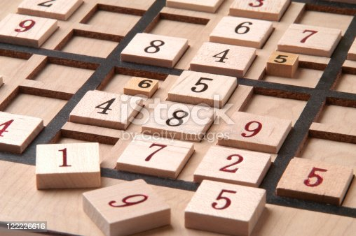 Close up of a wood Sudoku Game Board with puzzle in progress.