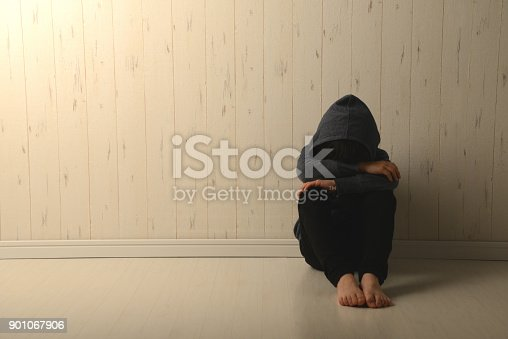 istock Suffering child in dark room 901067906