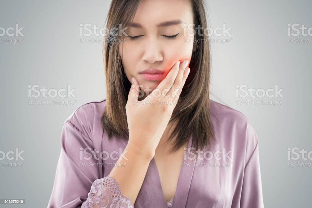 Suffering from toothache. Beautiful young woman suffering from toothache while standing against grey background stock photo