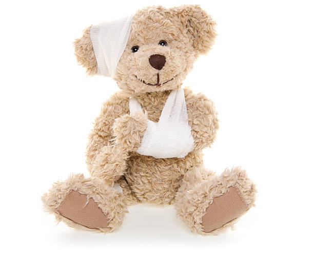 Suffering Injured Sweet Teddy Bear Injured Teddy Bear with arm sling and bandage. teddy bear stock pictures, royalty-free photos & images