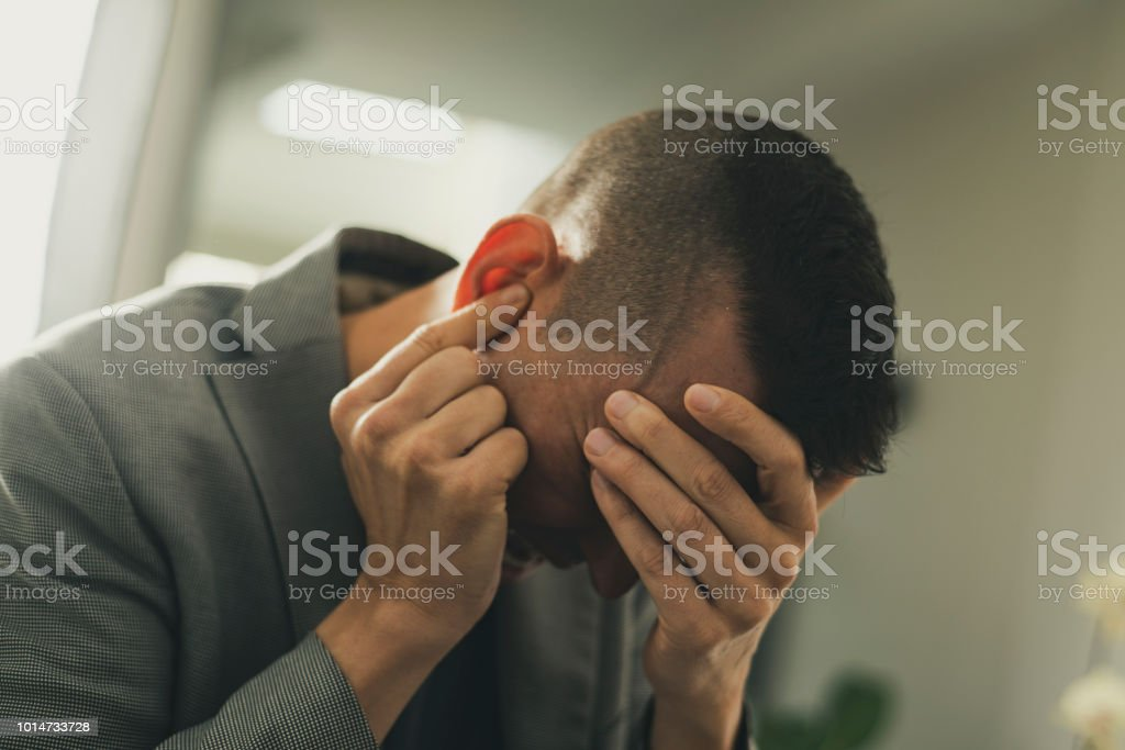 suffering man with his hands in his head stock photo