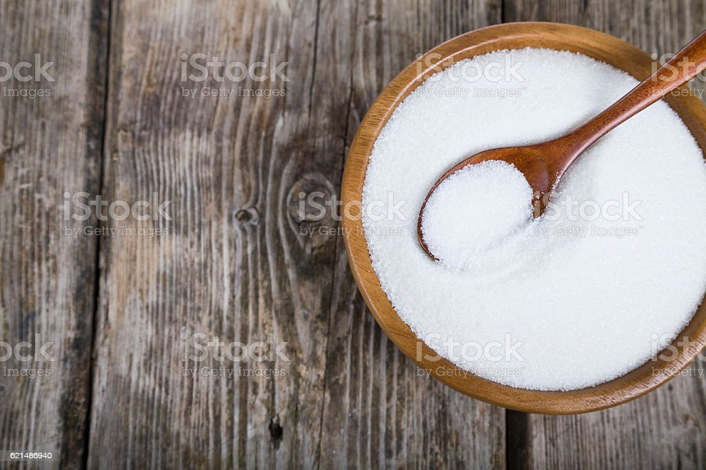 Sugar and spoon in a wooden bowl photo libre de droits