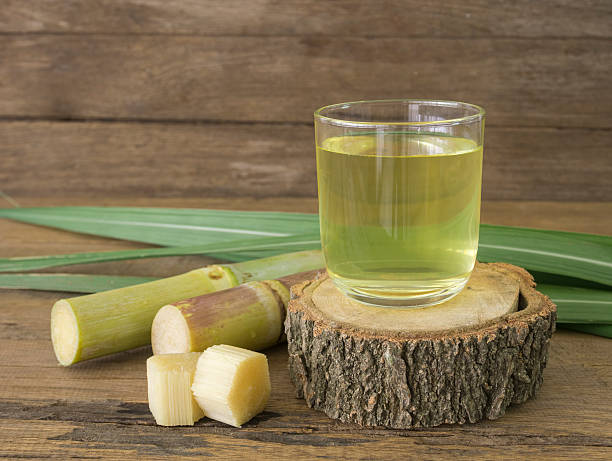 sugar cane juice Freshly squeezed sugar cane juice in glass with cut pieces cane on a wooden table. sugar cane stock pictures, royalty-free photos & images