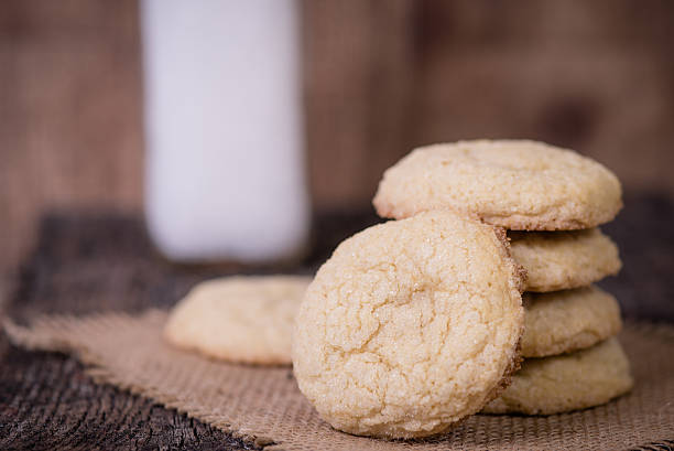 Sugar cookies and milk Sugar cookies piled up with jar of milk blurred in background. sugar cookie stock pictures, royalty-free photos & images