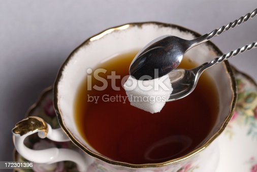 Sugar Cube in Silver Tongs over Tea Cup
