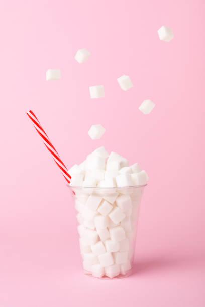 zuckerwürfel fallen in glas auf rosa hintergrund ungesunde ernährung konzept - würfelzucker stock-fotos und bilder