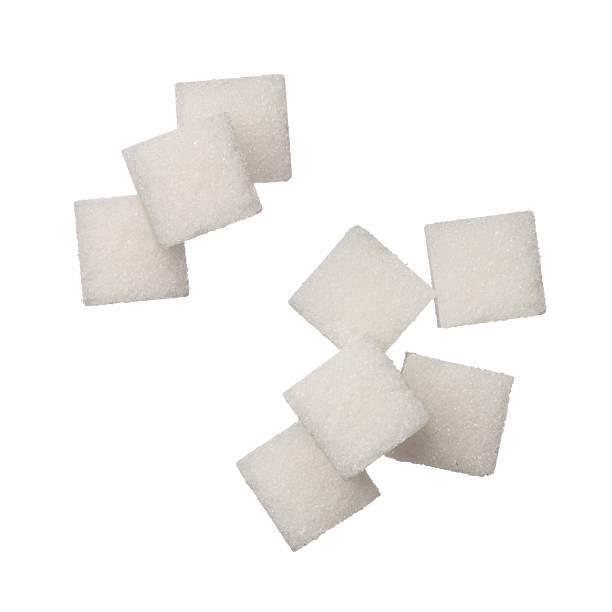 Sugar cubes free falling on white background stock photo
