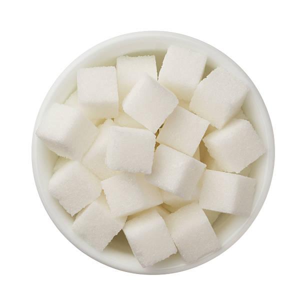 zucker würfel in einer schüssel isoliert auf weißem hintergrund - würfelzucker stock-fotos und bilder
