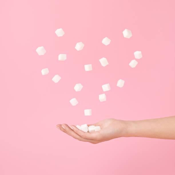 Zuckerwürfel in der Hand und fliegende Zuckerwürfel in Herzform auf Pastellrosa. – Foto