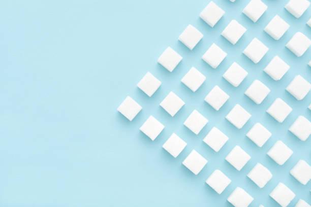 zuckerwürfel muster auf blauem hintergrund mit kopierraum - würfelzucker stock-fotos und bilder