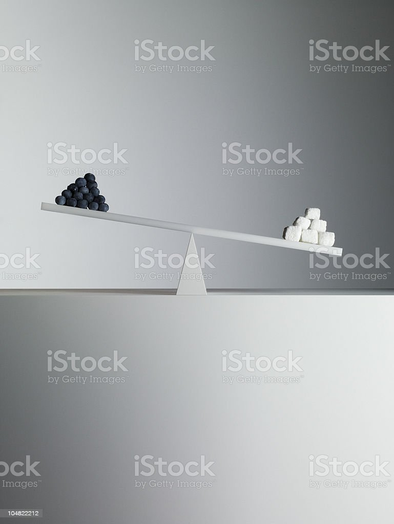 Sugar cubes tipping seesaw with blueberries on opposite end stock photo