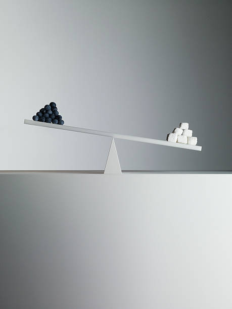 sugar cubes tipping seesaw with blueberries on opposite end - imbalance stock photos and pictures