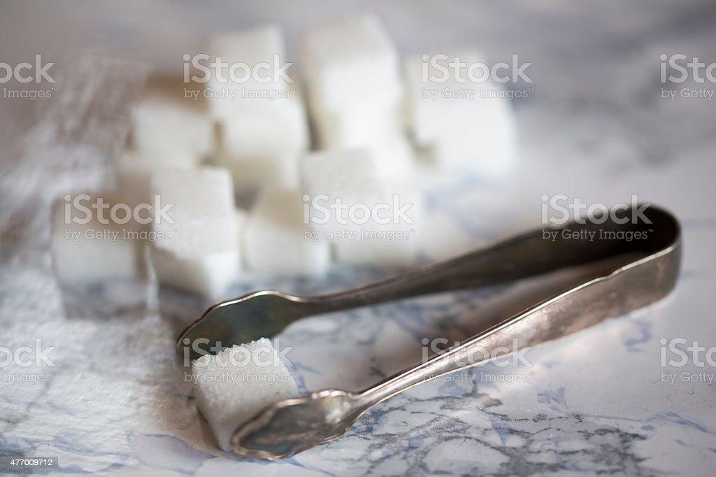 Sugar cubes with sugar tongs stock photo