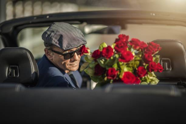 Sugar Daddy Eyes Seduction Sugar Daddy Eyes Seduction. Attractive Caucasian Men with Roses Awaiting His Girlfriend While Seating in a Convertible Car. age contrast stock pictures, royalty-free photos & images