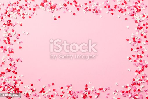 istock Sugar hearts frame on pink background. Romantic, St Valentines day concept. Top view. Copy space. 1130138672