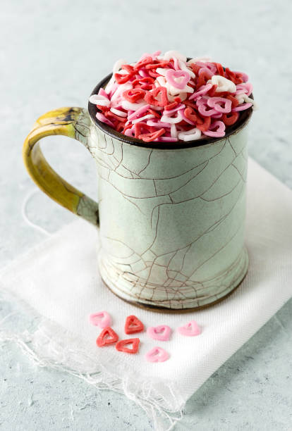 Sugar hearts in a cup on delicate background - foto stock