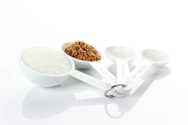 Sugar in measuring spoons on white background stock photo