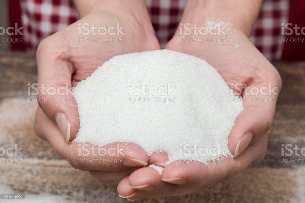 Sugar in the hands on the wooden table in the kitchen. Sweet meal. stock photo