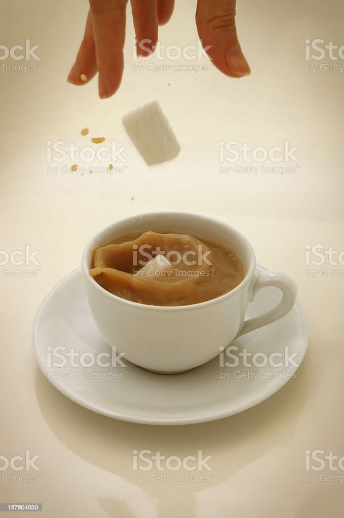 Sugar Lumps Falling into a Cup of Tea stock photo