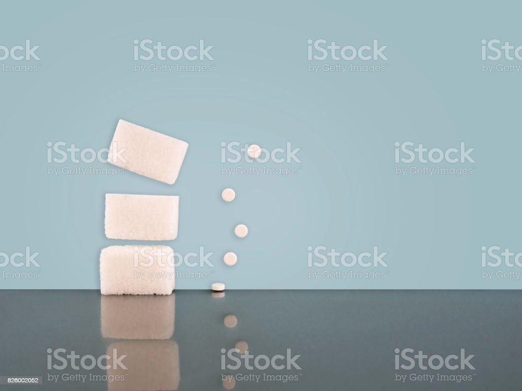 Sugar or artificial sweetener. Both on pale blue background. stock photo