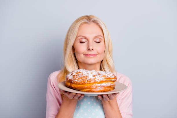 socker doft doft aromatisk människor person koncept. närbild porträtt av lugn lugn nöjd söt härlig romantisk med modern frisyr mormor lukta fräsch god kaka isolerade på grå bakgrund - food woman to smell bildbanksfoton och bilder