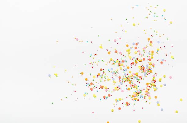 sugar sprinkle dots on white background. sweet decoration for cakes. top view, copy space. - confetti stock pictures, royalty-free photos & images